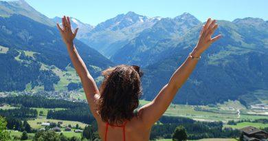 en plaine nature femme bras levés pour vivre le moment présent et respirer
