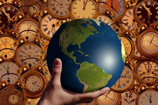 la terre dans une main et les horloges - moment présent